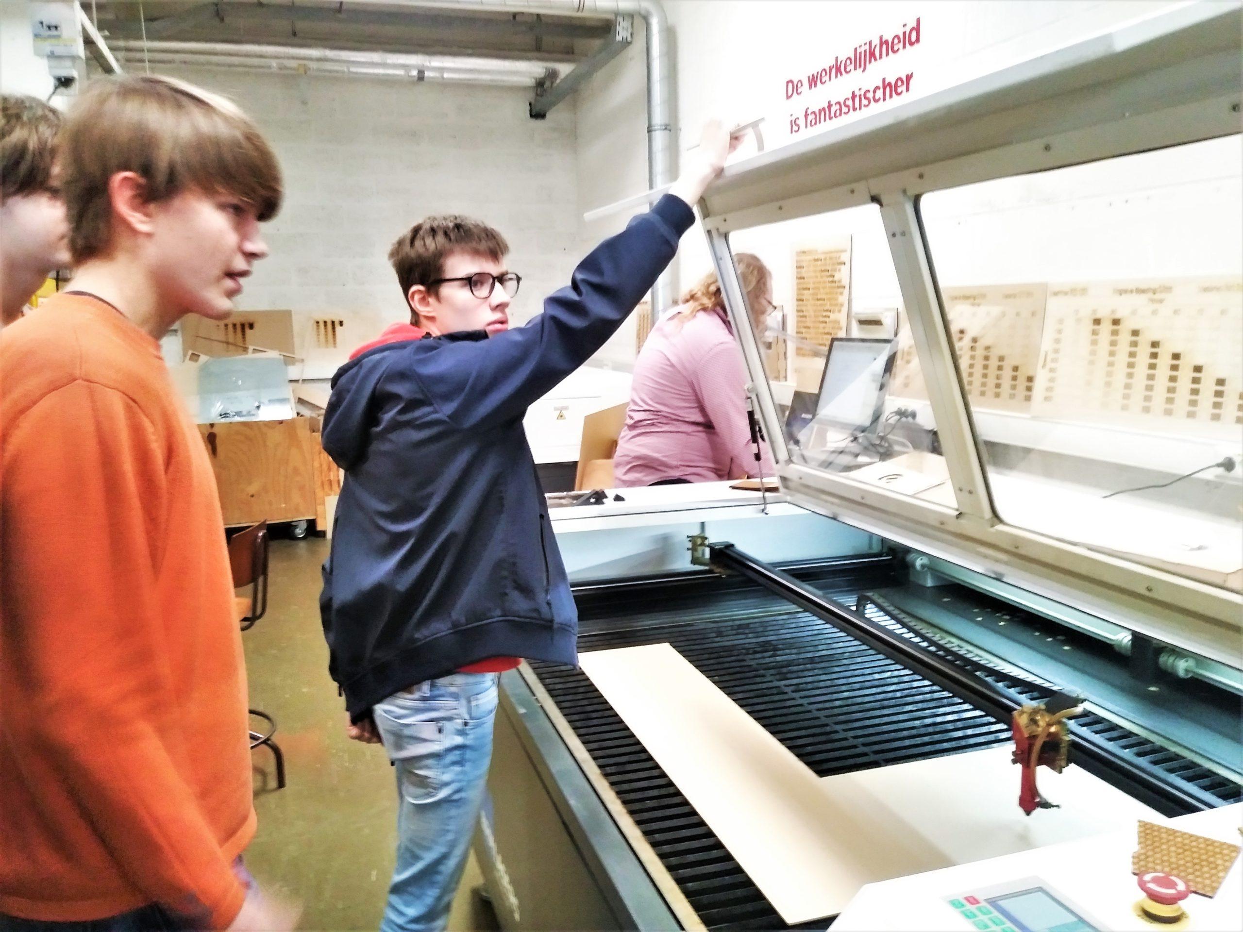 Enkele jongeren gebruiken een machine tijdens een bezoek aan FabLab