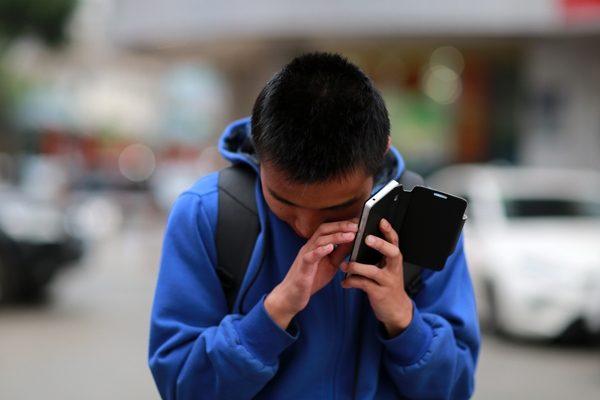 Jonge met visuele beperking gebruikt aangepaste mobile telefoon op straat