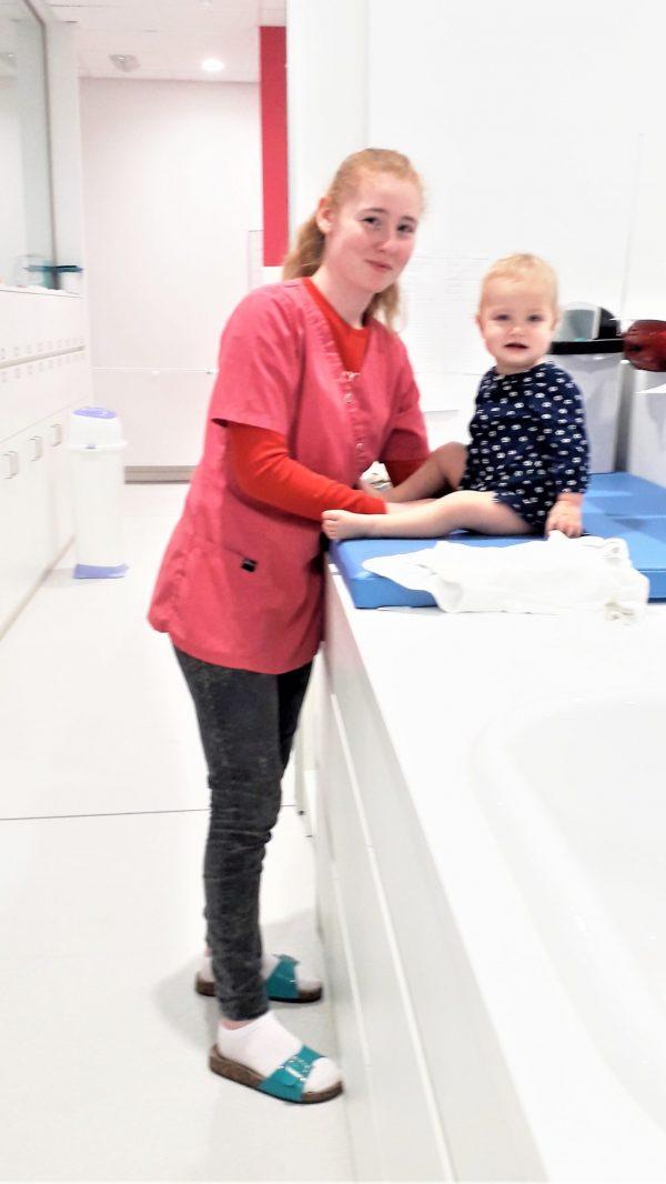 Medewerkster kinderdagverblijf en baby op verzorgingskussen